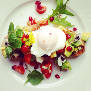 Poached Egg with avocado, pomegranate, tomato, chilli and edible flowers